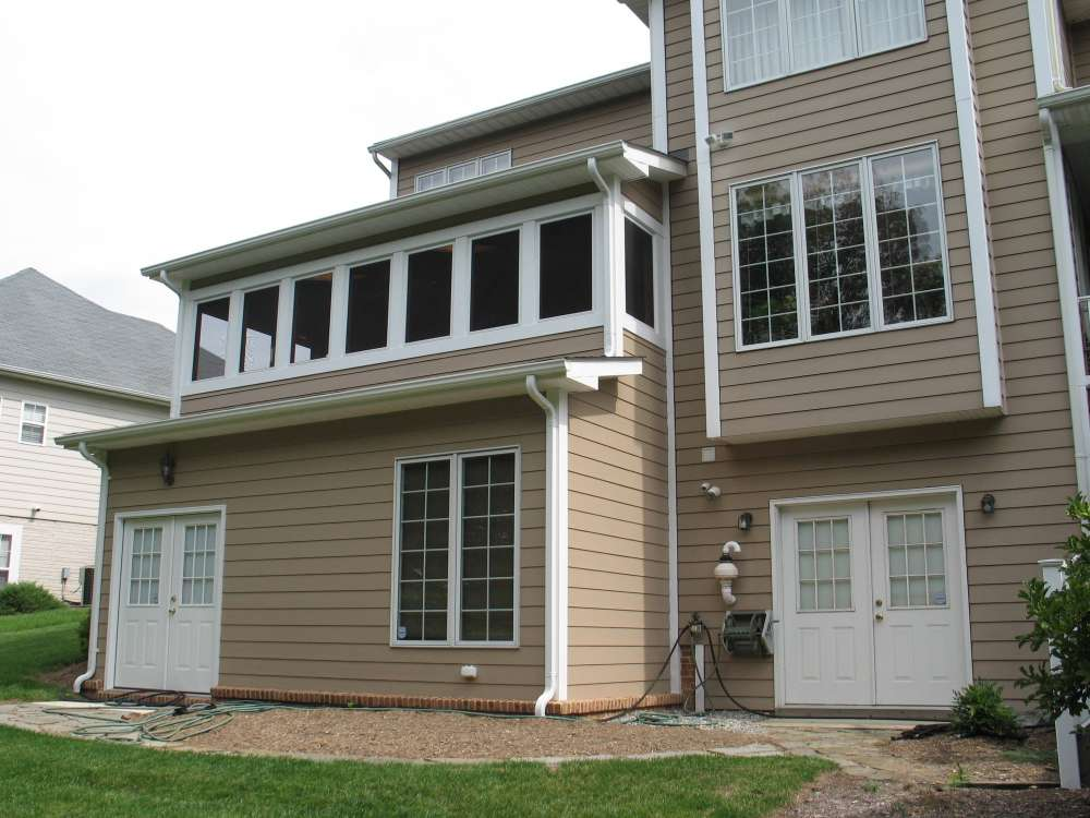Exterior view of a 2 story addition with a basement workshop and an all season porch on top.